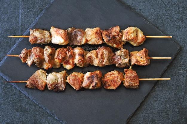 Smakelijke blozende kebabs op een donkere stenen ondergrond. bovenaanzicht