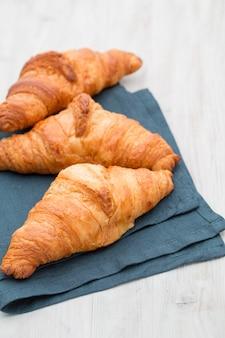 Smakelijke boterachtige croissants op oude houten tafel.