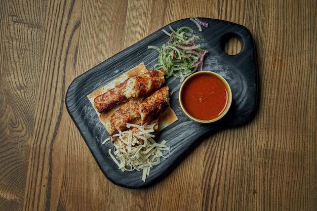 Smakelijke broodjes lyulya kebab - gekookt boven een lamsgehakt met een bijgerecht pita en salsa op houten dienblad. houten oppervlak, oost-keuken. bovenaanzicht