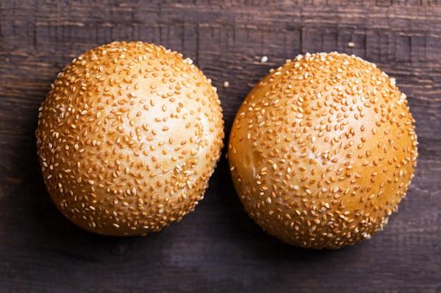 Smakelijke broodjes voor sandwich met sesamzaadjes op de houten tafel