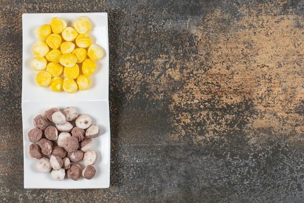 Smakelijke bruine en gele snoepjes in blauwe kom.
