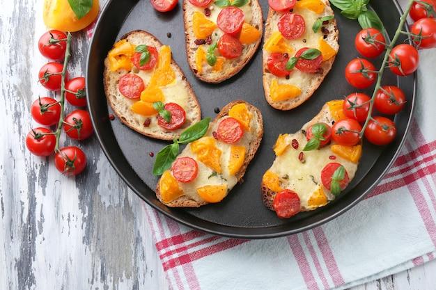 Smakelijke bruschetta met tomaten op pan, op oude houten tafel