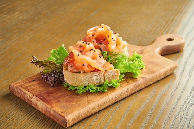 Smakelijke bruschetta met zalm en sla op een snijplank op een houten muur. close-up, selectieve aandacht