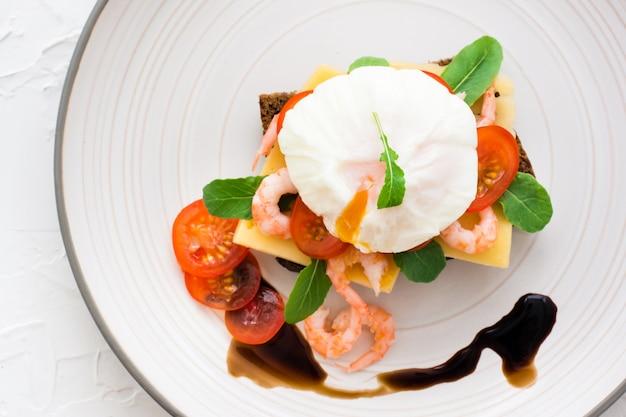 Smakelijke bruschetta op roggebrood met gepocheerd ei, tomaat, garnalen en rucola op een bord. bovenaanzicht