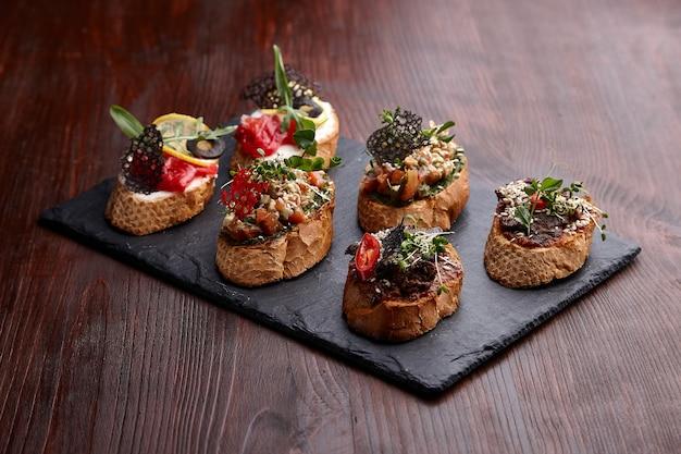 Smakelijke bruschettas op een stenen standaard op een houten tafel