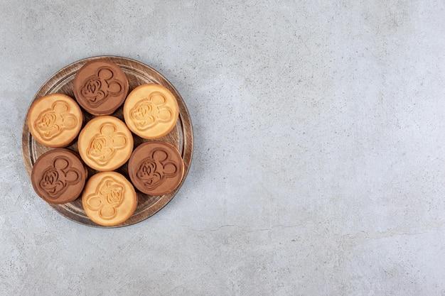 Smakelijke bundel koekjes op houten bord op marmeren achtergrond. hoge kwaliteit foto