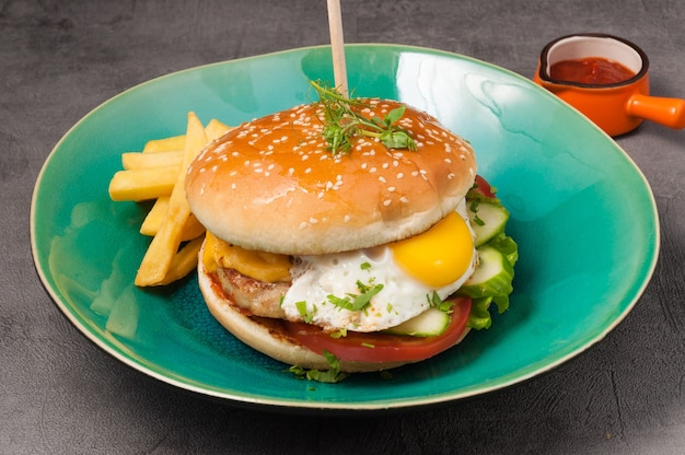 Smakelijke burger met kipkotelet en ei met tomatensaus en frites