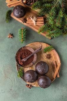 Smakelijke cacaobommen met marshmallow en chocolade op houten plaat met dennentakken en kruiden
