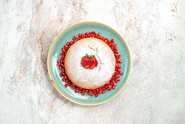 Smakelijke cake blauw bord cake met aardbeien en zaden van granaatappels op de roze tafel