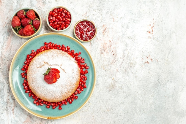 Smakelijke cake een smakelijke cake met aardbeien naast de schalen met aardbeien zaden van granaatappel aan de linkerkant van de tafel