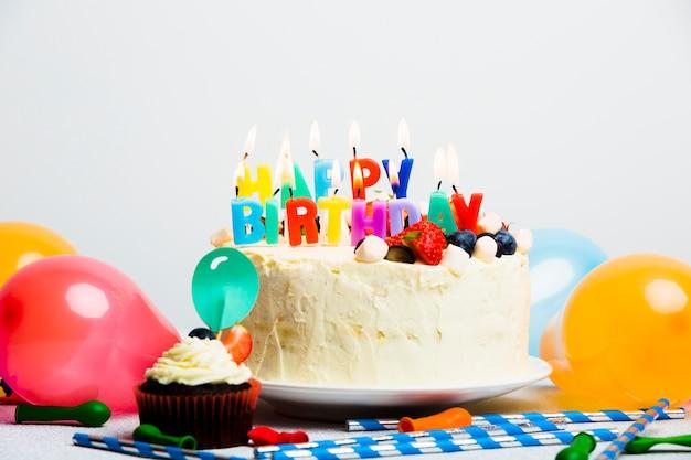 Smakelijke cake met bessen en gelukkige verjaardagstitel dichtbij ballons