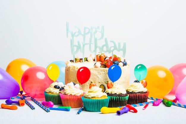 Smakelijke cake met bessen en gelukkige verjaardagstitel dichtbij reeks muffins en ballons