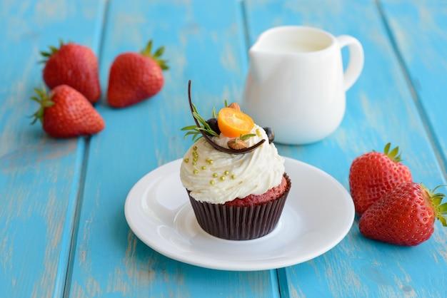 Smakelijke cake met stukjes fruit en aardbei op een tafel