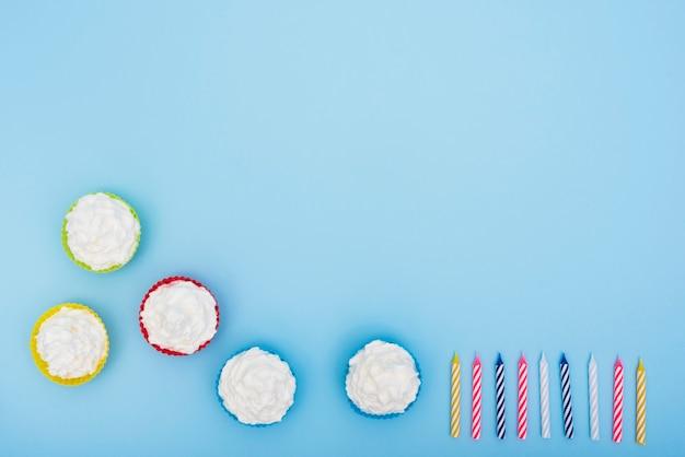 Smakelijke cakes en kaarsen op blauwe achtergrond