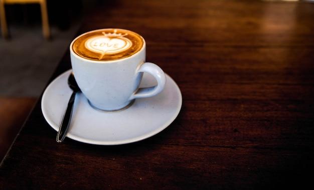 Smakelijke cappuccino staat op de houten textuurtafel met liefdeskunst