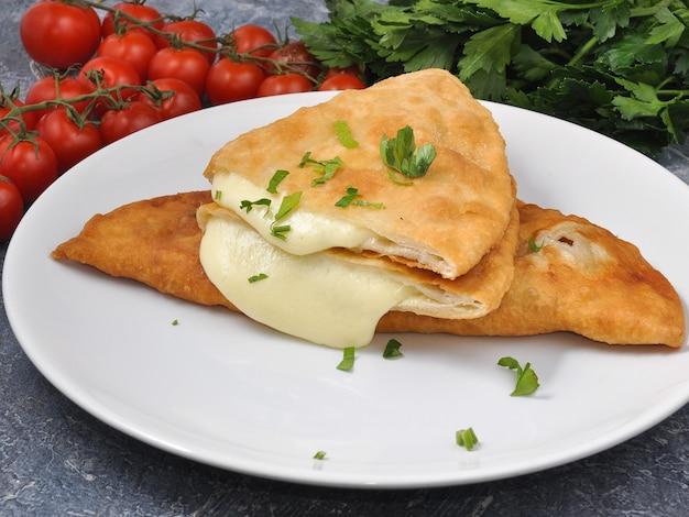 Smakelijke cheburek met kaas en kruiden op een witte plaat