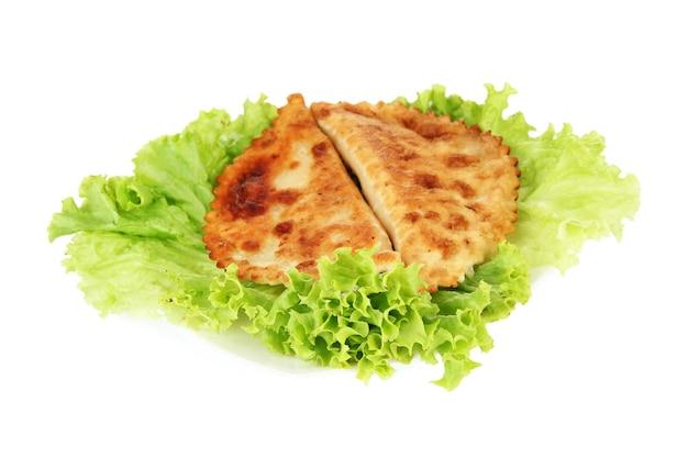 Smakelijke chebureks met verse kruiden op plaat, close-up