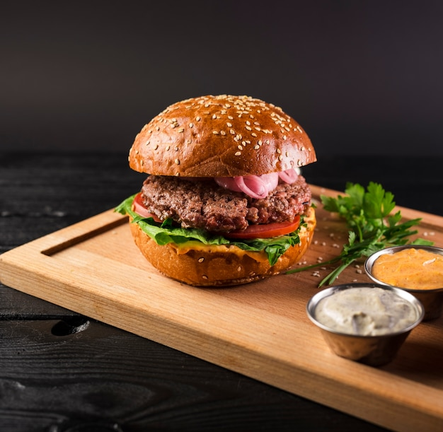 Smakelijke cheeseburger op een houten bord klaar om te worden geserveerd