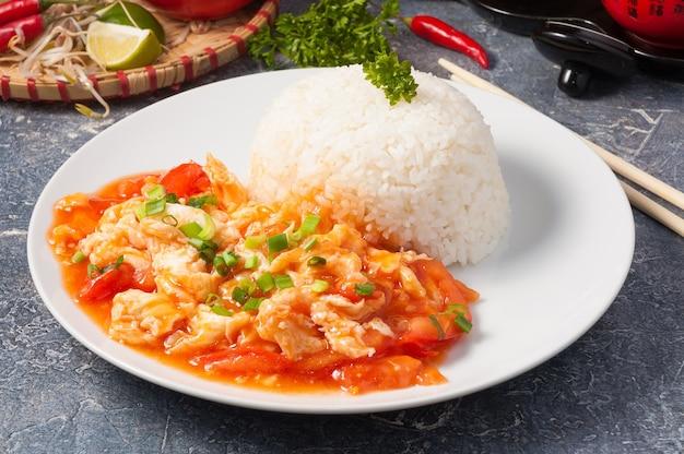 Smakelijke chinese omelet met tomaten en rijst op een witte plaat