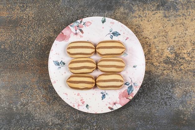 Smakelijke chocolade gestreepte koekjes op kleurrijke plaat.