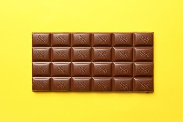 Smakelijke chocoladereep op gele achtergrond. zoet eten