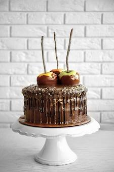 Smakelijke chocoladetaart met appels op bakstenen muur