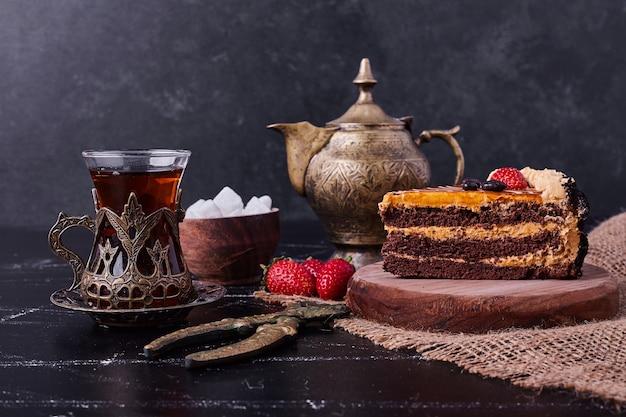 Smakelijke chocoladetaart met theeset op donkere achtergrond.