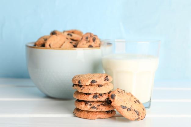 Smakelijke chocolate chip cookies en glas melk op houten tafel