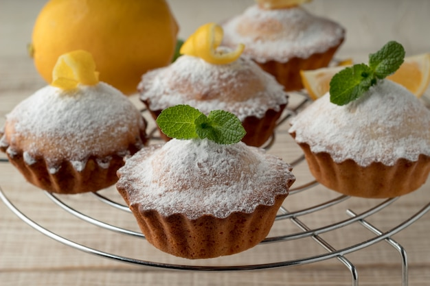 Smakelijke citroenmuffins met suikerpoeder op koelrek