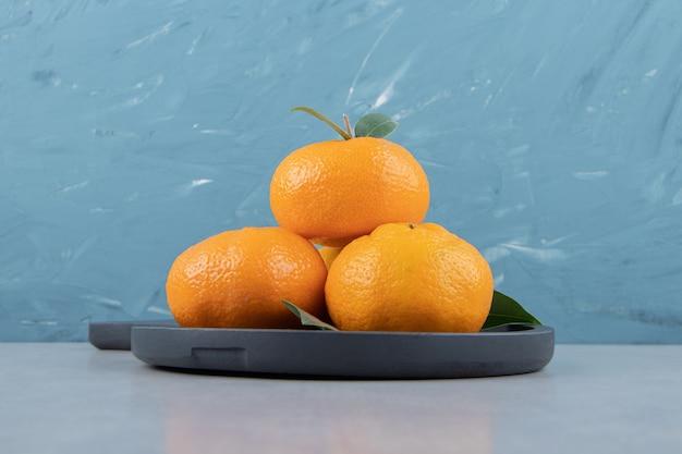 Smakelijke clementinevruchten op zwart bord