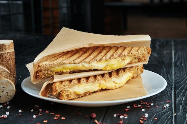 Smakelijke clubsandwich in toastbrood met gesmolten kaas, in ambachtelijk papier op een zwarte houten ondergrond