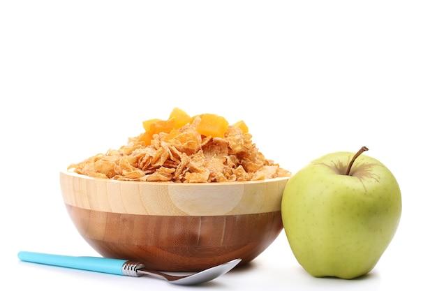 Smakelijke cornflakes in houten kom en appels op wit wordt geïsoleerd