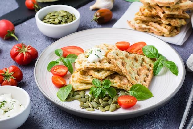 Smakelijke courgettewafels, tomaten en pompoenpitten op een bord op tafel. plantaardig dieet vegetarisch eten