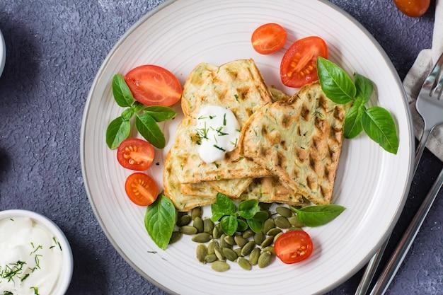 Smakelijke courgettewafels, tomaten en pompoenpitten op een bord op tafel. plantaardig dieet vegetarisch voedsel. detailopname. bovenaanzicht