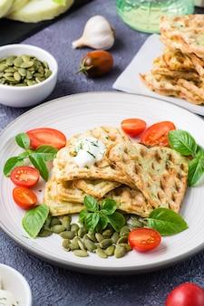 Smakelijke courgettewafels, tomaten en pompoenpitten op een bord op tafel. plantaardig dieet vegetarisch voedsel. verticale weergave. detailopname