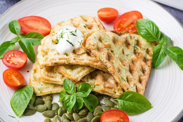 Smakelijke courgettewafels, tomaten, pompoenpitten en basilicum op een bord op tafel. plantaardig dieet vegetarisch voedsel. detailopname