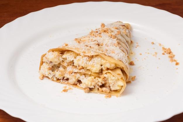 Smakelijke crêpe met banaan en kokosschaafsel op een witte plaat