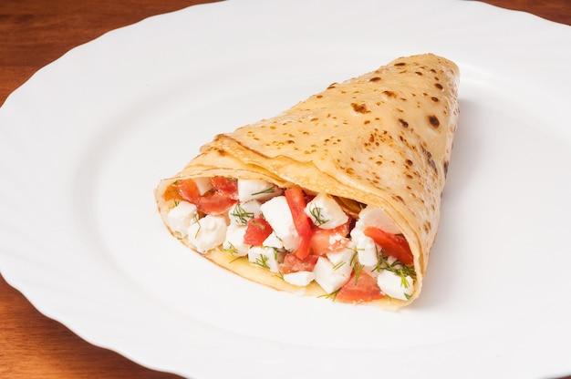Smakelijke crêpe met tomaten en kaas op een witte plaat