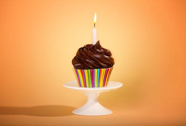 Smakelijke cupcake op kleuroppervlak