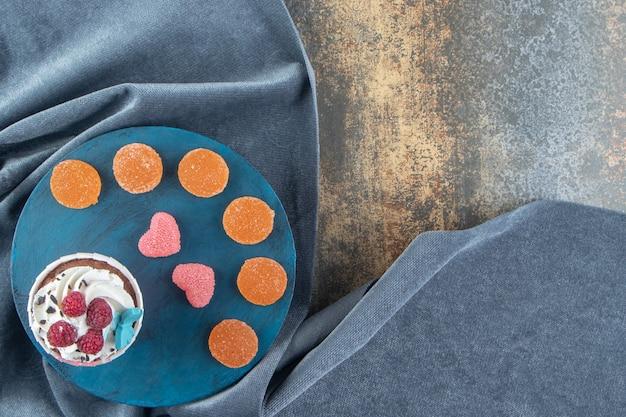 Smakelijke cupcake versierd met room en snoepjes op blauw bord