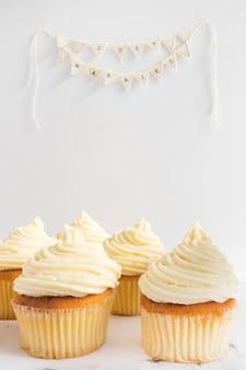 Smakelijke cupcakes en net getrouwd gors op witte achtergrond