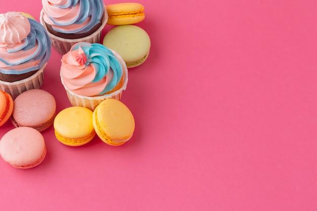 Smakelijke cupcakessnoepjes op roze dichte omhooggaand
