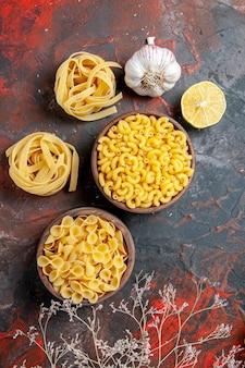 Smakelijke dinerbereiding met ongekookte pasta's in verschillende vormen en knoflook op gemengde kleurenachtergrond