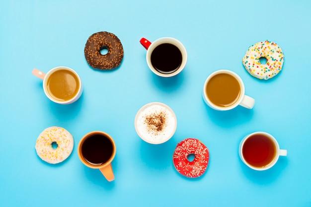 Smakelijke donuts en kopjes met warme dranken, koffie, cappuccino, thee op een blauwe ondergrond. concept van snoep, bakkerij, gebak, koffieshop, vergadering, vrienden, vriendelijk team. plat lag, bovenaanzicht