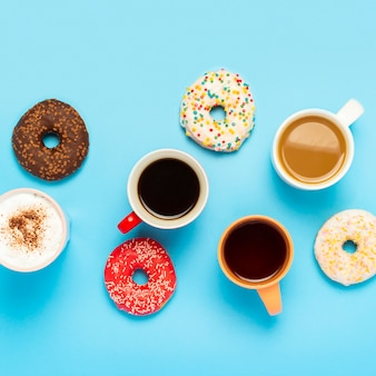 Smakelijke donuts en kopjes met warme dranken, koffie, cappuccino, thee op een blauwe ondergrond. concept van snoep, bakkerij, gebak, koffieshop, vergadering, vrienden, vriendelijk team. plein. plat lag, bovenaanzicht