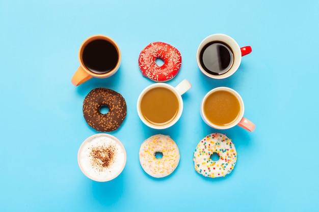 Smakelijke donuts en kopjes met warme dranken, koffie, cappuccino, thee op een blauwe ondergrond.