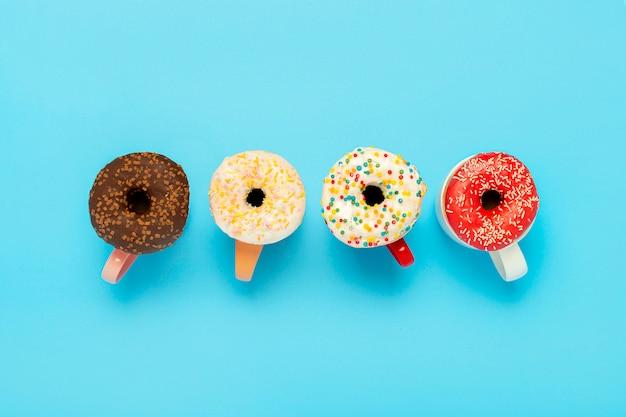 Smakelijke donuts en kopjes met warme dranken op een blauwe ondergrond. concept van snoep, bakkerij, gebak, koffieshop. . plat lag, bovenaanzicht