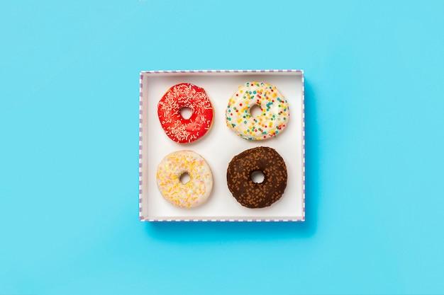 Smakelijke donuts in een doos op een blauwe ondergrond. concept van snoep, bakkerij, gebak, koffieshop. . plat lag, bovenaanzicht