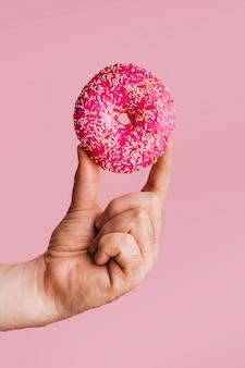 Smakelijke doughnut met het heldere in hand opdienen