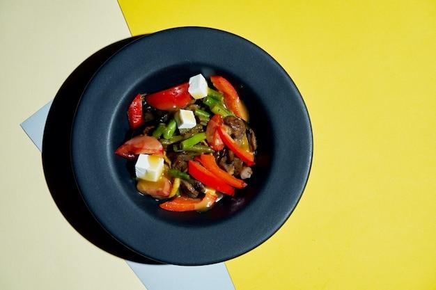 Smakelijke en gezonde vegetarische salade met grillgroenten, dressing en kaas in een zwarte kom op een gekleurd oppervlak bovenaanzicht op lekker eten